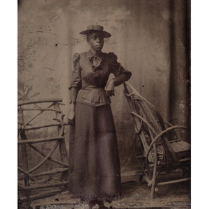 An African-American woman leaning on a chair.