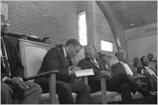Andrew Young, Martin Luther King, Jr., and others sitting behind the podium at a meeting in a church building in Greenville, Alabama.