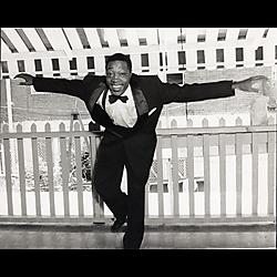 Man in tuxedo dancing on porch