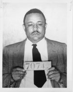 Mississippi State Sovereignty Commission photograph of B.D. Lambert after an arrest holding a slate bearing the the booking number 7074, Montgomery, Alabama, 1956 February