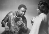Member of Bobby Moore and the Rhythm Aces speaking with a woman backstage, before or after performing at a dance at the National Guard Armory on Dallas Avenue in Selma, Alabama.