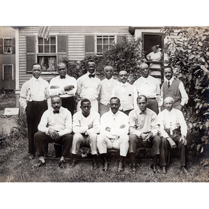 Twelve men pose for a group photograph