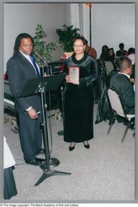Curtis King awarding unidentified woman at Christmas Kwanzaa soiree Christmas/Kwanzaa Soiree