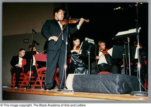 [Left low-angled shot of a man playing a violin, with other string musicians performing in the background] Christmas/Kwanzaa Concert