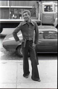 African American man wearing trendy clothes, wide collar, and bell-bottoms