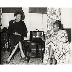 Hazel Scott and a woman reporter sitting with radio in domestic interior with leaf patterned curtains