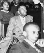Mississippi State Sovereignty Commission photograph of E. J. Stringer dressed in a suit and seated in the foreground of several African Americans wearing choir robes, Columbus, Mississippi, 1950s