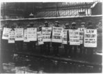 [British NAACP pickets with anti-lynching placards]