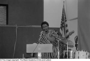 [Photograph of the drummer speaking into the microphone] Conference on Black Women in the Arts
