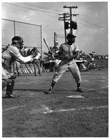 Action shot 1949 baseball with an African American slugger.