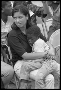 White woman in the Solidarity Day crowd at the Poor People's March on Washington, hugging an African American child while Coretta Scott King speaks