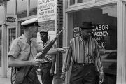 Police officer speaking to an African American man in front of a business down the street from 16th Street Baptist Church in Birmingham, Alabama, after the church was bombed.