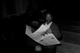 Man reading an issue of The Southern Courier during a meeting at First Baptist Church in Eutaw, Alabama.