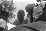 """Whitney M. Young, Jr., speaking to Martin Luther King, Jr., while seated on a platform in front of the state capitol in Jackson, Mississippi, at the end of the """"March Against Fear"""" begun by James Meredith."""