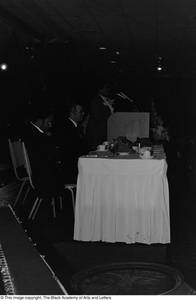 Photograph of a conference table, podium, and two unidentified individuals Jack Evans Breakfast with JBAAL