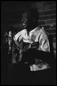 Josh White performing on guitar in a coffeehouse