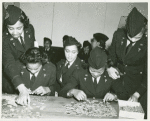 Two African American Lieutenants of the Women's Army Corps sitting at a table and working on jigsaw puzzles while three others assist and look on