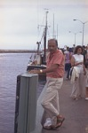 Man standing on dock [color photonegative]