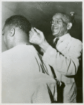African American veteran Joseph N. Stevens, 72, cutting the hair of an African American serviceman, Fort Benning, Georgia