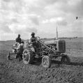 Men using a tractor and other equipment to prepare a field for planting in Autauga County, Alabama.