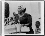 [Mahalia Jackson, half-length portrait, facing left, standing at podium, singing]