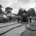 Firemen removing hoses from an engine during a civil rights demonstration in Talladega, Alabama.