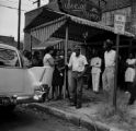 Juanita Jones hugging her sister, Maxine McNair, in front of Social Cleaners across from 16th Street Baptist Church, after the church was bombed.