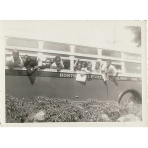 A group of boys hang out the window of a bus on the way to Breezy Meadows Camp.