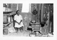 Myrtle Lawrence's neighbor. Young woman sits near the wood stove and cooking pots in substandard living conditions