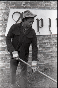 Young African American man working with a pitchfork