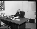 Doyle Mitchell at desk, Mar[ch] 1964 [cellulose acetate photonegative]
