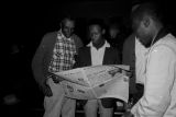 Men reading an issue of The Southern Courier during a meeting at First Baptist Church in Eutaw, Alabama.
