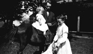 Unidentified man with children on a horse and dog.