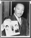 [Dr. Martin Luther King, half-length portrait, standing, facing front, holding photograph of three civil rights workers who were murdered]