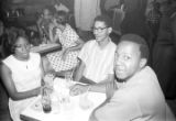 Barbara Howard Flowers and Robert Flowers seated with another man at a table at the Laicos Club in Montgomery, Alabama.