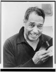 [Duke Ellington, head-and-shoulders portrait, autographing record album]