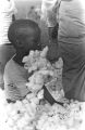 Young boy in the back of a trailer filled with cotton, parked at the field of Mrs. Minnie B. Guice near Mount Meigs in Montgomery County, Alabama.