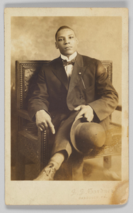 Photographic postcard of a seated man holding a bowler hat