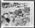 [African American parents and children stand across the street from School No. 34, as white pickets march, Baltimore, Maryland]