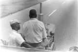 Two men riding a tractor down a paved road near Mount Meigs in Montgomery County, Alabama.