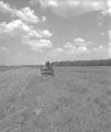 Two men operating a Massey-Harris combine in a field, probably in Autauga County, Alabama.