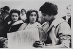 [Charlayne Hunter sitting with her classmates while reading through course work materials]