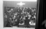 Man, possibly Fred Shuttlesworth, speaking to audience in a church building during a meeting.