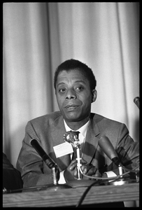 James Baldwin, seated on a panel at the Youth, Non-Violence, and Social Change conference, Howard University