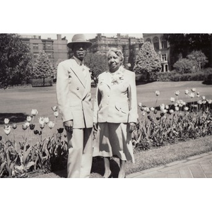 A man and woman stand on walkway bordered by tulips.