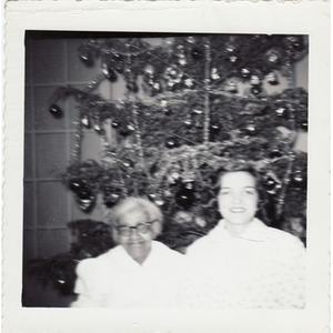 An elderly housekeeper sits beside a Christmas tree.