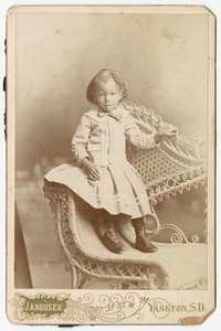 Photograph of a toddler standing on a wicker chair