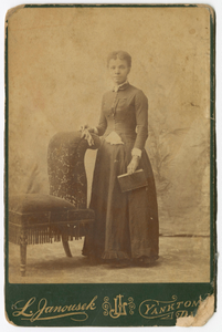 Photograph of a woman standing next to a chair and holding a book