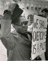 Man holding we shall overcome sign