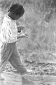 Young boy walking down a dirt road near Mount Meigs in Montgomery County, Alabama.